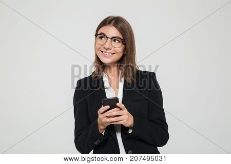 Portrait of a jovial pretty businesswoman in suit holding mobile phone and looking away at copy space isolated over white background