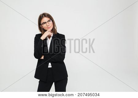 Portrait of smiling pretty businesswoman in suit and eyeglasses standing with arms folded and looking away at copy space isolated over white background