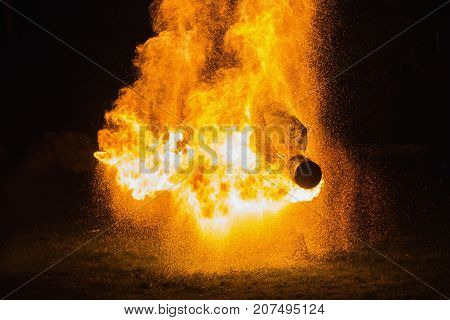 A stunning fire show against a dark night. A fire man in a chemical protection suit and a gas mask plays with fire. Fire show. Man in fire. Flame of fire in the night