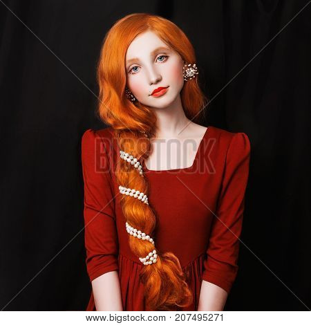 A cute red-haired woman with a scythe in a red dress on a black background. Woman with pale skin. Nice woman. Woman with long hair. Woman in a red dress. Woman on a black background.