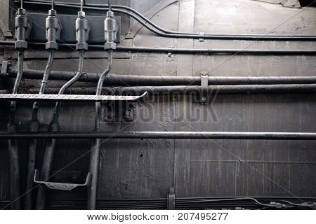 Hydraulic hoses as well as steam pipes and water pipes on a boiler of an old steam locomotive.