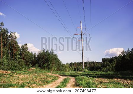 Electric power tower over blue summer sky. Electric wire. The dirt road goes into the green forest with electric power tower. Electric line. Electric energy.