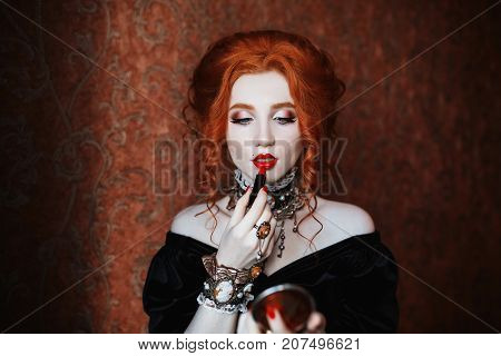 Gothic model with lipstick. A woman with lipstick paints lips. Vampire with pale skin and red hair in a black dress with red lipstick. Girl witch with lipstick and vampire claws and red lips. Lipstick in hand. Outfit for halloween.