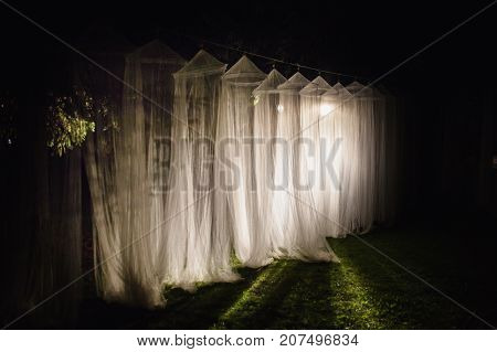 The white long canopyare illuminated by the light of the lantern on a dark night. Conceptual photography with canopy. White canopy. Canopy at night