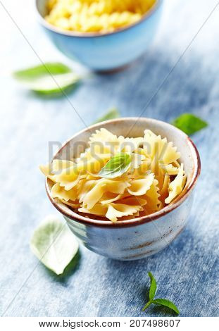 Dried pasta (farfalle) in a ceramic bowl