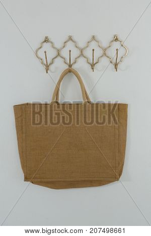 Bag hanging on hook against white wall