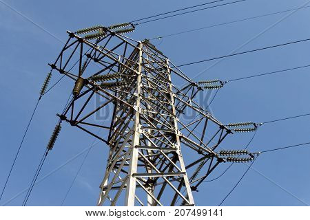 Electric pylon against the backdrop of the blue sky on a summer day