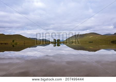 Beautiful lake with reflections of the trees and surrounding mountains in the Scottish Highlands in Scotland United Kingdom; Concept for travel in Scotland