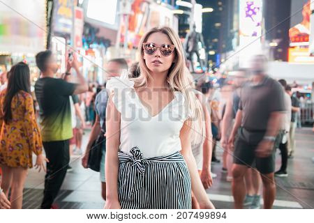Fashionable young woman traveling in New York City Time Square and walking in the crowd at night time