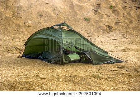 green broken camping tent on the beach at the stormy weather
