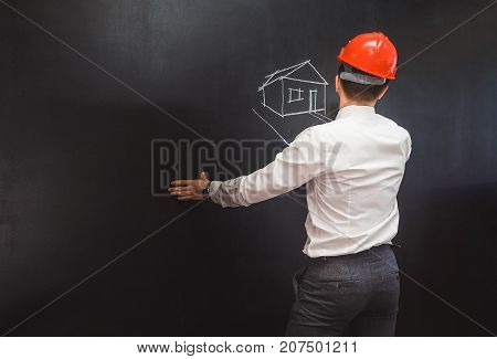man in a white shirt and in an orange helmet draws a house plan with chalk on a blackboard