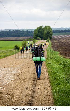 rear of hiker teenage girl walking on the rural road