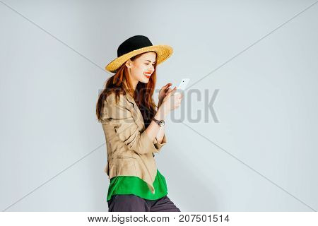 girl in a hat with red lips looks at the phone and smiles, happy moment