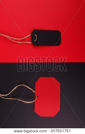 Close-up of a black tag on a red background and a red tag on a black background.