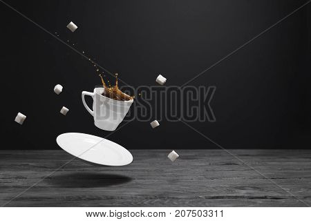 Floating cup of coffee saucer and lump sugar over a black wooden table. Splashes of black coffee in a white cup. Black background for advertisement and text.