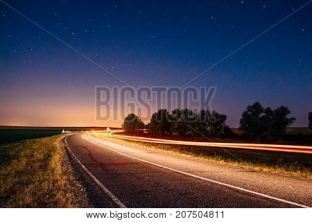 A beautiful summer landscape with highways and tracks from car headlights. Night dark blue sky with stars above the horizon