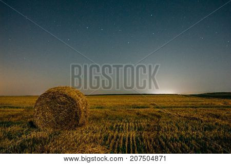 A Ursa Major in the night sky. Rural field with a stack of dry hay