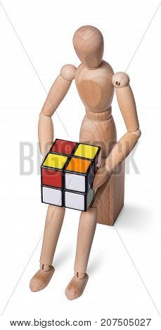 Wooden dummy trying to collect the Rubik cube. Isolated on white background.