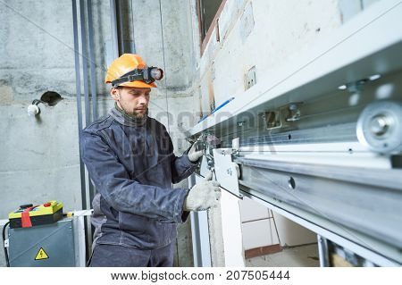 machinist with spanner adjusting lift mechanism in elevator shaft