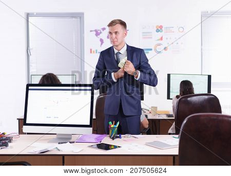 A young businessman puts money in the pocket of his jacket. A big plan is a desktop with a computer, a stationery, a tablet.