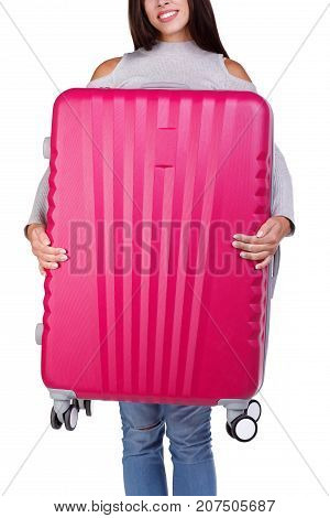 Smiling happy girl holding huge pink suitcase and presents on the camera. A roomy and stylish suitcase for girls on a long trip around the world. Close-up of suitcase.