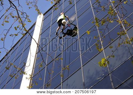 Unrecognisable high rise window cleaning worker cleans an office building. Real people. Copy space