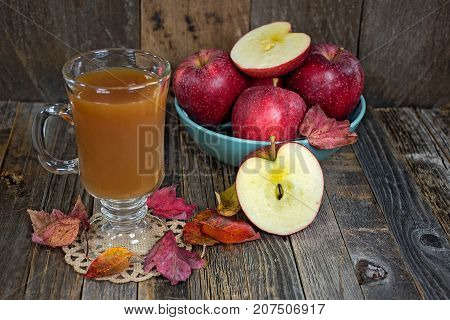 apple cider in glass mug with autumn leaves and red apples on weathered wood