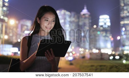 Woman looking at tablet computer in city