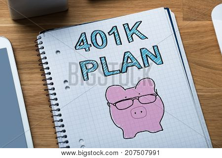 Close-up Of Sketched 401k Pension Plan With Piggybank On Notebook On Wooden Table