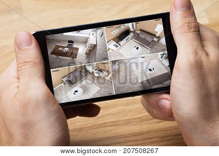 Person's Hand Holding Smartphone And Monitoring Video Footage Against Wooden Table