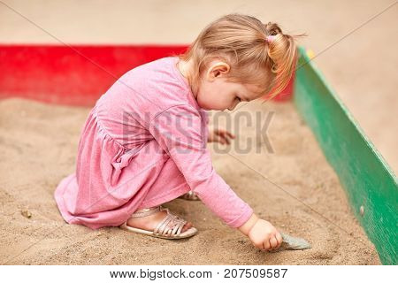 Close-up of a little blonde in a pink dress playing in a sandbox.