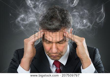 Portrait Of Mature Businessman Suffering From Headache