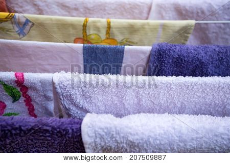 Closeup image of several colorful towels hanging on dryer after washing