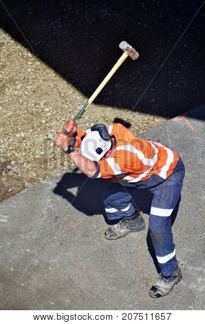 Road Worker Holds A Heavy Hammer And Strikes Concert
