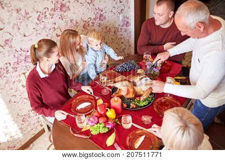 Multi-generation, cheerful family at the Thanksgiving dinner on a blurred background. Grandfather serving traditional roasted turkey on Thanksgiving.