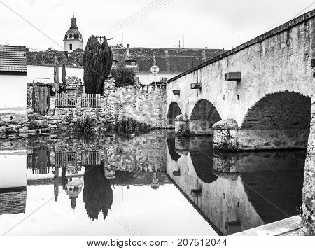 Old stone bridge reflected in calm water, Putim, Southern Bohemia, Czech Republic. Black and white image.