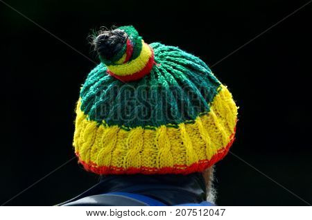 Rear view of unrecognizable man wearing a Bob marley hat abstract background. Copy space