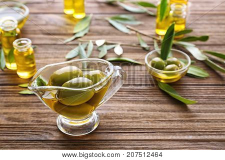 Glass gravy boat with olive oil on wooden table