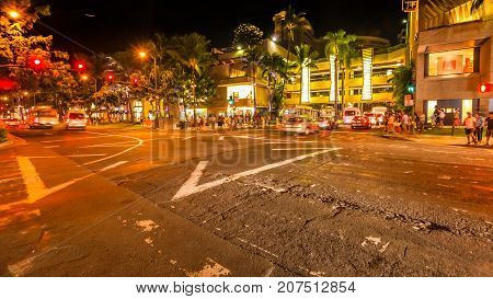 Waikiki crossroad at night. People moving for shopping and cars crossing the streets. City night lights and nightlife concept. HONOLULU, OAHU, HAWAII, United States.