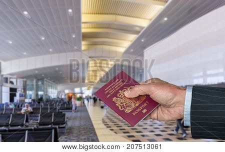 Senior caucasian businessman arm holding a UK passport to show to official in airport terminal for international flight
