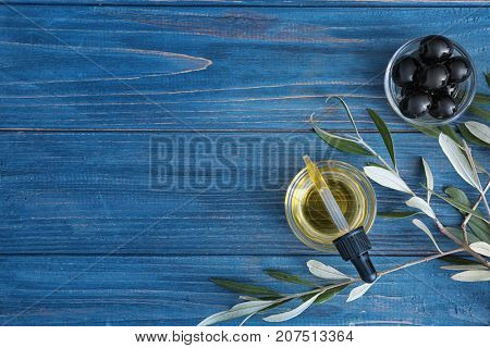 Glass bowl and pipette with olive oil on wooden table