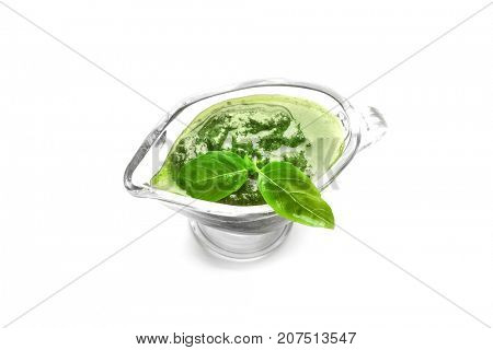 Gravy boat with delicious basil pesto sauce on white background