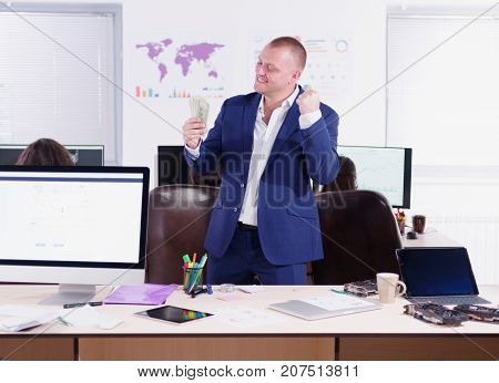 A young businessman rejoices in success. A big plan is a desktop with a computer, stationery, a tablet and a video card. Cryptocurrency.
