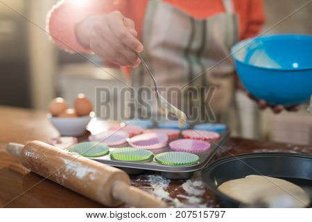 Mid section of woman putting muffin batter in paper case in baking tray