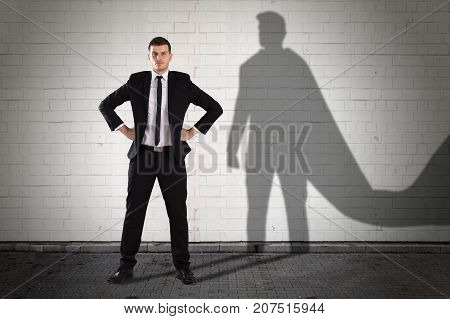 Shadow Of Superhero Formed On Wall Behind The Young Businessman
