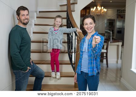 Portrait of woman holding house key while sitting on stairs