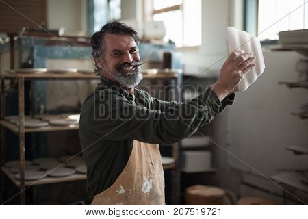 Portrait of male potter checking ceramic bowl in pottery workshop