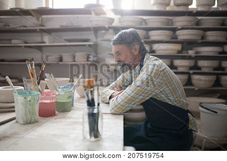 Thoughtful male potter sitting at worktop in pottery workshop