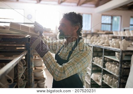 Male potter placing craft product on shelf in pottery workshop