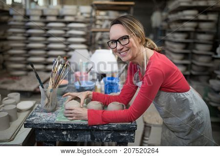 Portrait of woman checking mugs at worktop in pottery workshop
